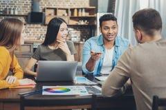 Ambitny cztery kolegi dyskutuje pomysł zdjęcia stock