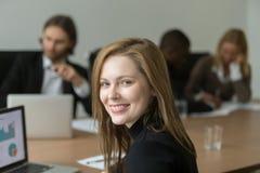 Ambitny uśmiechnięty młody bizneswoman przy drużynowym spotkaniem, przewodzi strzał Zdjęcie Stock