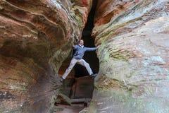 Ambitny wycieczkowicz decyduje wspinać się w ogromny szczelinowym zdjęcie stock