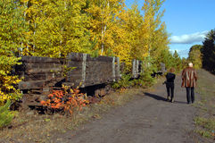 Amble besides Coal Cars. Couple explore a backroad above Quincy Copper Mine and discover old wooden, ore cars rotting amoung the fall foliage of upper penninsula Royalty Free Stock Photo