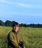 Amble through Field. Young man kneels in a meadow near sunset.  He is smiling happily and wearing jeans and olive long sleeved shirt Stock Photos