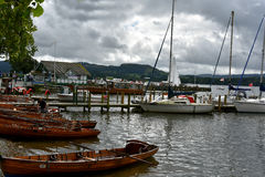 Ambleside. Harbor at Ambleside in Lake district  overlooking Windermere Lake. Rowboats, sailboats and cruise boats at the pier of an english resort Stock Photo