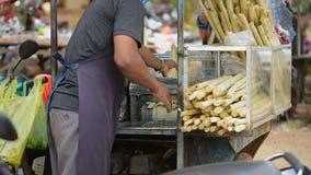 ambodian Mann, der Zuckerzuckerrohrsaft unter Verwendung der Maschine auf der Straße extrahiert stock video
