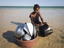 Girl washes dishes on the beach stock image