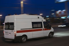 A ambulância vai na cidade da noite Imagens de Stock Royalty Free