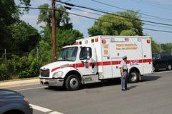 A ambulância viaja após tráfegos de direção do polícia fotografia de stock