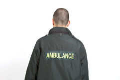 Ambulance. An ambulance driver shot with his back to the camera against a white background Royalty Free Stock Image