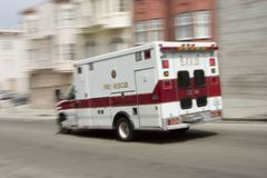 Ambulance 3. An ambulance blazes by, it's sirens whaling. An intensional camera blur gives a feeling of a rushed tension to the scene royalty free stock photo