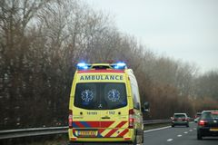 Ambulance with blue flashing lights and sirens on motorway A44 in the Netherlands. Ambulance with blue flashing lights and sirens on motorway A44 in the stock photos