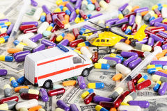 Ambulance car and helicopter toys through dollars and pills Royalty Free Stock Photos