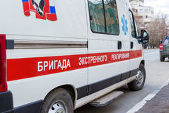 Ambulance car parked up in the street. Text on russian: Stock Images