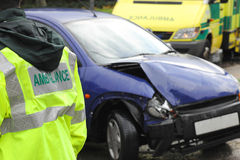 Ambulance at a car crash. A damaged vehicle rests at the side of the highway following a collision. An ambulance and medic stand by Royalty Free Stock Image