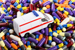 Ambulance car toy through the pills. (installation on the theme of modern medicine trends stock image