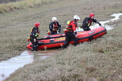 Ambulance crew river rescue training. A four man rescue inflatable raft training and practicing tugging this boat over the marshy land to the shallow river Stock Photography