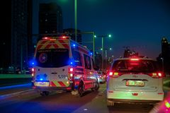 Ambulance crossing other vehicle with full speed while Flashing hazard lights. December 29, 2018 - Abu Dhabi, UAE: Ambulance crossing other vehicle with full royalty free stock photo