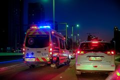 Ambulance crossing other vehicle with full speed while Flashing hazard lights. December 29, 2018 - Abu Dhabi, UAE: Ambulance crossing other vehicle with full royalty free stock photography