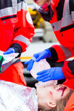Ambulance doctor giving oxygen to female victim Stock Image