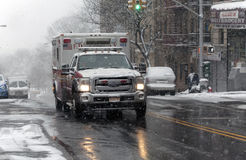Ambulance drives through street in snow storm Stock Photo