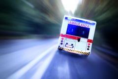 Ambulance on the Go. Rear view of Italian ambulance lorry on the move for emergency call. Intentional camera motion blur gives a feeling of a rushed tension to royalty free stock photography