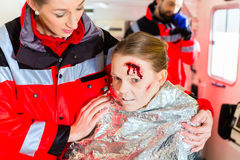 Ambulance helping injured woman Royalty Free Stock Photo
