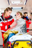 Ambulance helping injured woman Royalty Free Stock Images