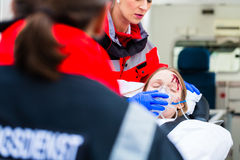 Ambulance helping injured woman on stretcher Royalty Free Stock Images