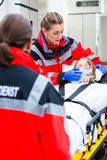 Ambulance helping injured woman on stretcher Royalty Free Stock Image