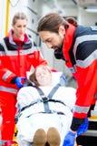 Ambulance helping injured woman on stretcher Stock Photo