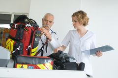 Ambulance man and woman checking gear between interventions royalty free stock image