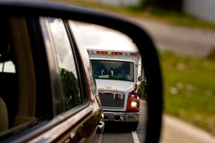 Ambulance in Mirror. View of ambulance approaching in side view mirror Stock Photo