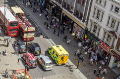 Ambulance in Oxford Street. LONDON, UK  JUNE 17, 2014: View from above of an ambulance driving up the wrong side of Oxford Street in Central London.  The busy Royalty Free Stock Image