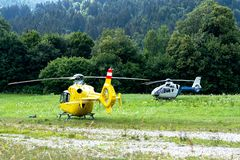 Ambulance and police helicopters landed in a mountainous village in the field.  stock image