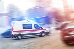 Ambulance racing through city traffic jam on slippery road with slush snow. Car accident on highway stock photography