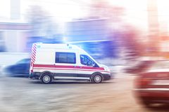 Ambulance racing through city traffic jam on slippery road with slush snow. Car accident on highway royalty free stock image