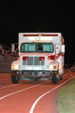Ambulance at sports event. An ambulance parked on an athletic track at night.(front view Stock Photography