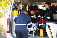 Ambulance team. Pulling a stretcher out of vehicle royalty free stock image