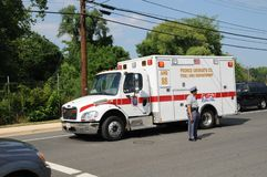 Ambulance travels past a policeman directing traffics stock photography