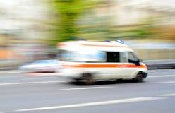 Ambulancia en el movimiento que conduce abajo del camino Foto de archivo libre de regalías