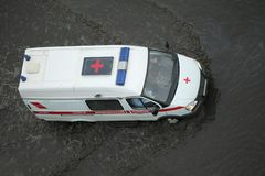 Ambulansbil som går till och med den översvämmade vägen fotografering för bildbyråer