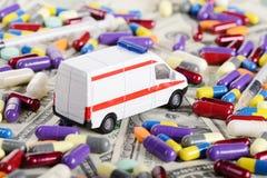 Ambulansowa samochód zabawki przejażdżka przez dolarów, pigułki i  Fotografia Stock