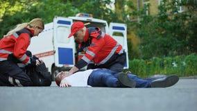 Ambulansowy załoga bieg obsługiwać lying on the beach na drodze, pierwsza pomoc przy wypadek samochodowy sceną zbiory