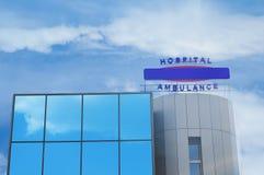 Ambulanza di costruzione dell'ospedale contro il cielo con la nuvola fotografie stock libere da diritti