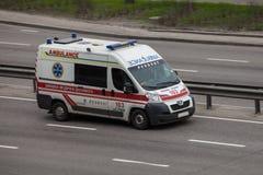 Ambulanza di Peugeot che accelera sulla strada principale vuota immagine stock