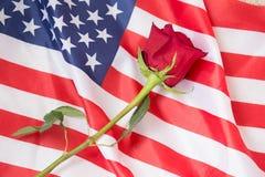 Ame àqueles que sacrificaram suas vidas para nós com uma rosa e uma bandeira americana fotos de stock