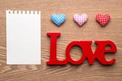 Ame corações vermelhos do guingão e anule a nota no fundo de madeira da textura Imagem de Stock Royalty Free
