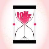 Ame el concepto con reloj de arena y la arena de disminución en el fondo rosado texturizado Fotos de archivo libres de regalías