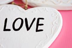 Ame el corazón blanco de madera en el fondo rosado, compositi horizontal Fotos de archivo