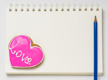 Ame el libro del espacio en blanco del cuaderno del diario con el lápiz Galleta en forma de corazón en una página en blanco del d fotografía de archivo libre de regalías