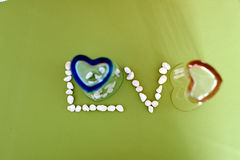 Ame el texto del vidrio de la forma del corazón y de poca piedra imágenes de archivo libres de regalías
