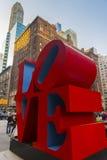 Ame a escultura e os turistas que passam perto no Midtown Manhattan Fotografia de Stock Royalty Free